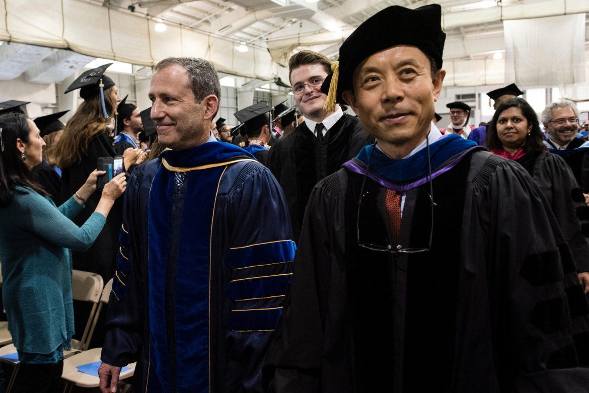 05/21/2016 - Medford/Somerville, Mass. - James Glaser, Dean of Arts and Sciences and Jianmin Qu, Dean of the School of Engineering, stride together to the platform to begin the Baccalaureate Service on the eve of Tufts University's 160th Commencement on Saturday, May 21, 2016. (Alonso Nichols/Tufts University)